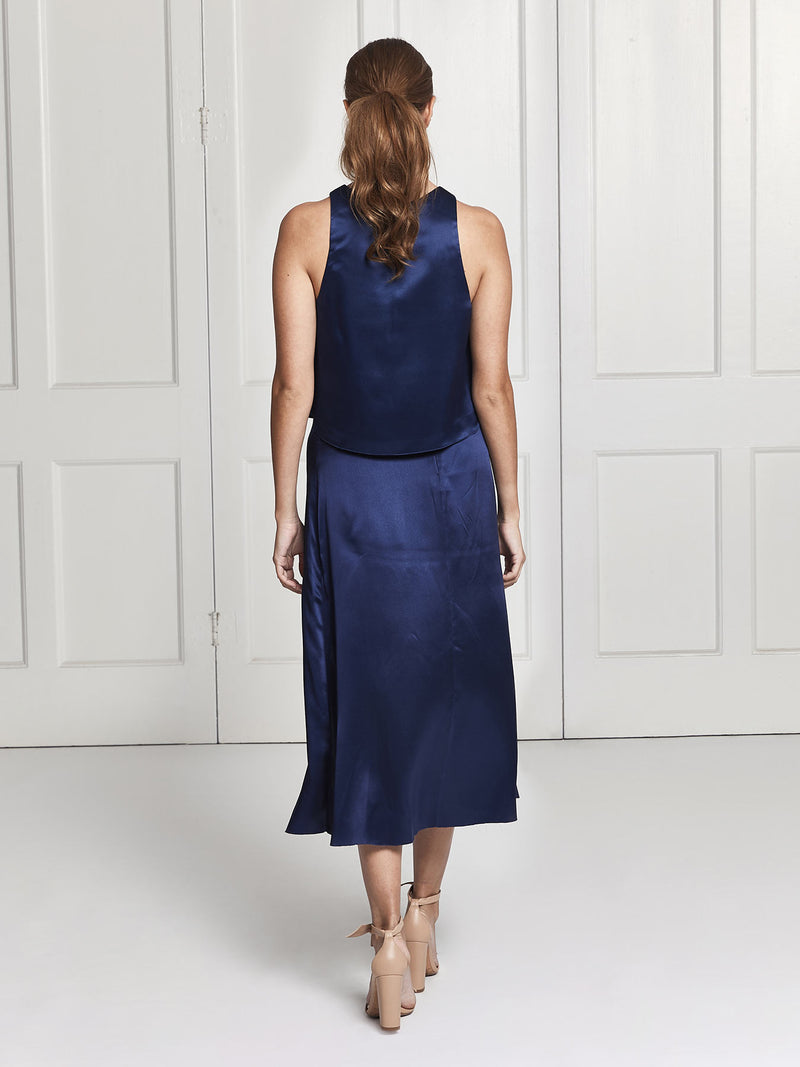 The rear view of the Eve midi silk skirt and top set in blue worn by Heloise Agostinelli