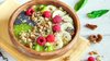 green smoothie bowl topped with fruit and nuts