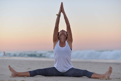 yoga teacher sitting on the beach at sunrise with arms up