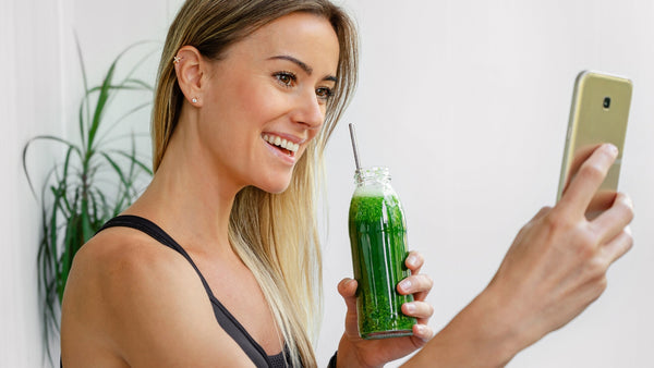 woman taking a selfie of her holding a green drink in a glass bottle