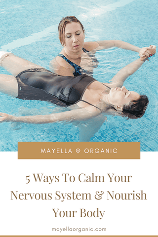 """Pinterest image for this blog post. The photo in the top half is the same photo as above of the two women in a pool for watsu treatment. The bottom half is the name of the blog post in gold text that reads """"5 Ways To Calm Your Nervous System and Nourish Your Body"""""""