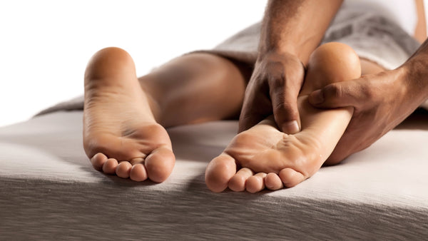 Close up of a person's feet while they are laying on their stomach on a massage table. The masseuse has two hands on the client's left foot pressing pressure in with the thumb.