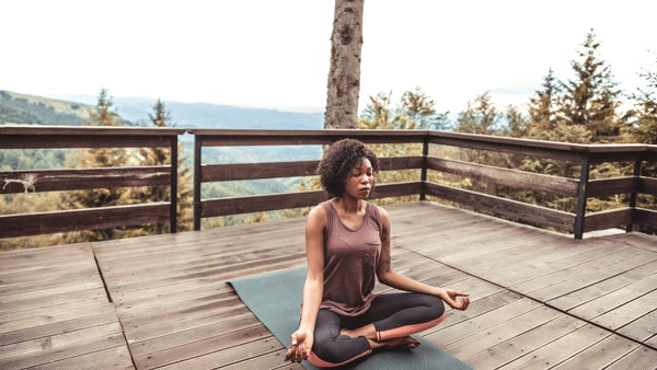 A woman sitting in a cross-legged meditation position on a yoga mat. She is outdoors on a timber balcony and there is a background of hills and nature. She is wearing a brown tank top and black yoga pants. She has chin-length dark brown curly hair.
