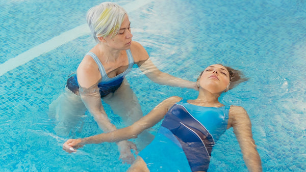 Two women in a swimming pool for a watsu treatment. One woman is floating with her eyes closed while the other woman is supporting her and facilitating the treatment.