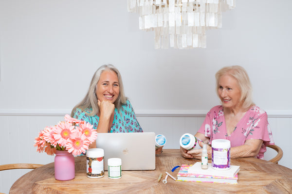 Amanda and Robyn are sitting at a timber dining table in front of a macbook laptop and four of their products. They are in floral dresses and smiling