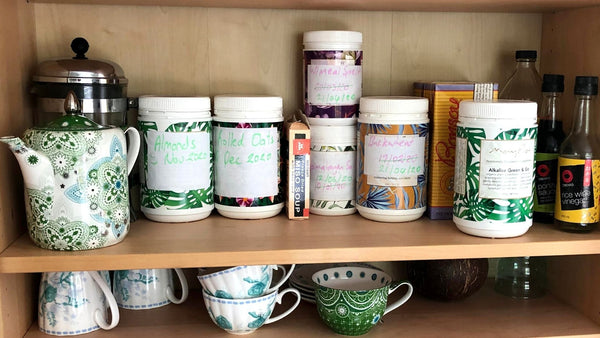 mayella containers in a pantry reused for pantry staples and relabelled by hand above a shelf of tea cups