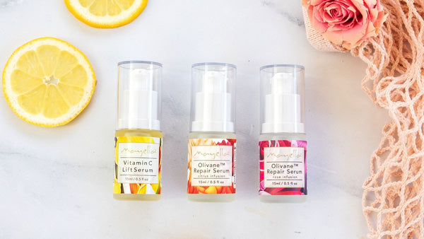 three Mayella serums in glass containers lying flat on a marble bench next to slices of lemon