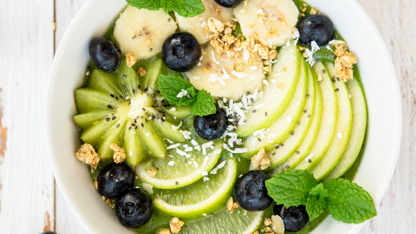 green smoothie bowl toped with kiwi blueberries apple and mint