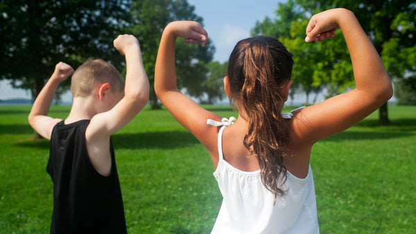 young girl and boy showing strong arms