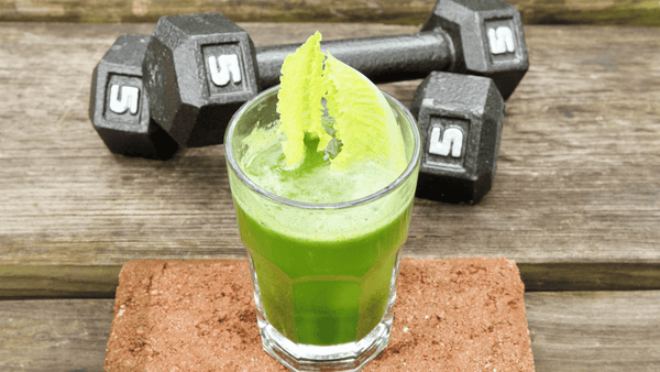 glass of light green liquid on top of a cork exercise block next to two dumbells crossed over each other