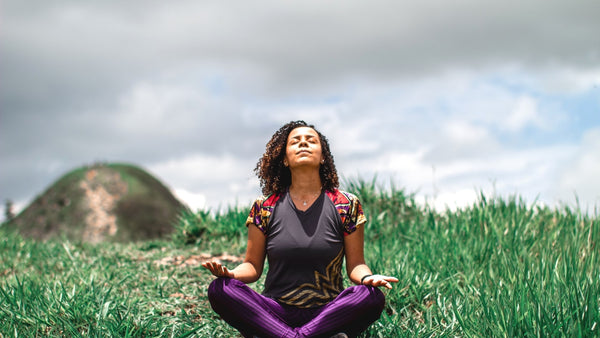 Photo of a woman sitting cross-legged on the grass. She is breathing calmly with her head tilted towards the sky. Her hands are on her knees with the palms facing upwards.
