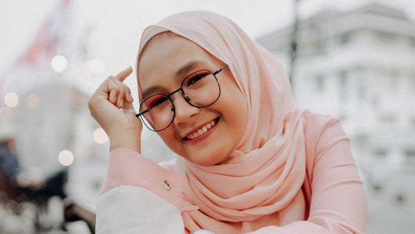smiling woman wearing a soft pink hijab