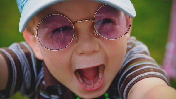 close up image of an excited toddler with retro purple glasses