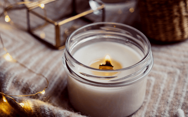small white candle burning in a clear, glass jar next to a gold and glass mini jewellery box and mini fairy lights