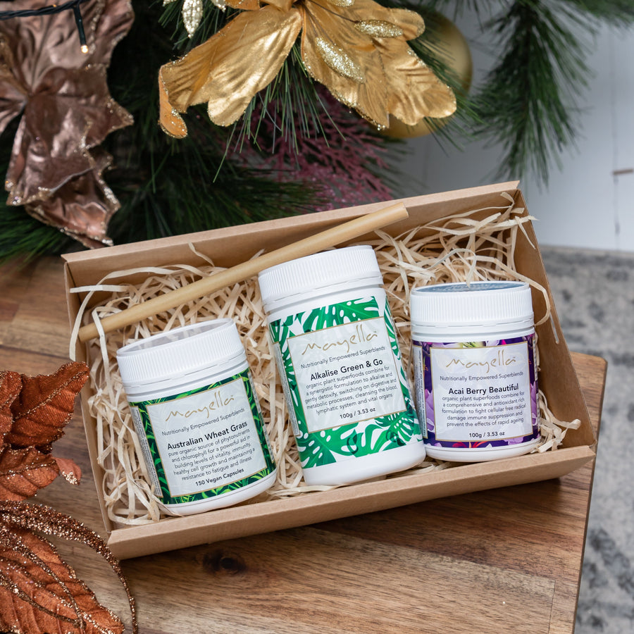 Wheatgrass Capsules, Alkalise Green & Go and Acai Berry Beautiful packed in a cardboard gift box with a bamboo straw with two gold-painted pine cones in the front