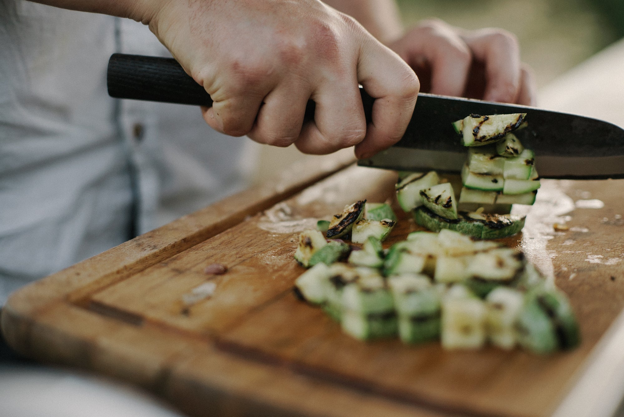 man chopping grilled zucchini on a wooden cutting board