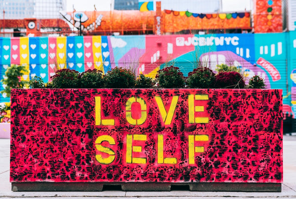 colorful red mural with yellow words stating love self