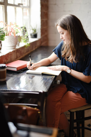 woman journaling in a coffee shop