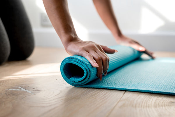 pair of hands rolling up a teal yoga mat