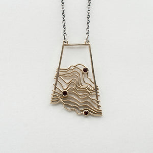 Brass Topographic Pendant with Garnets on a White Background