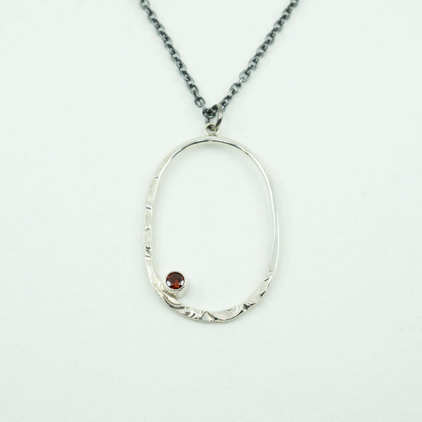Close view of a Silver Oval Pendant with a Garnet on a white background