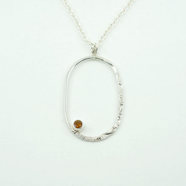 Close view of a Silver Oval Pendant with a Fire Opal on a white background