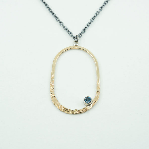 Close view of oval gold-filled pendant with a london blue topaz on a white background