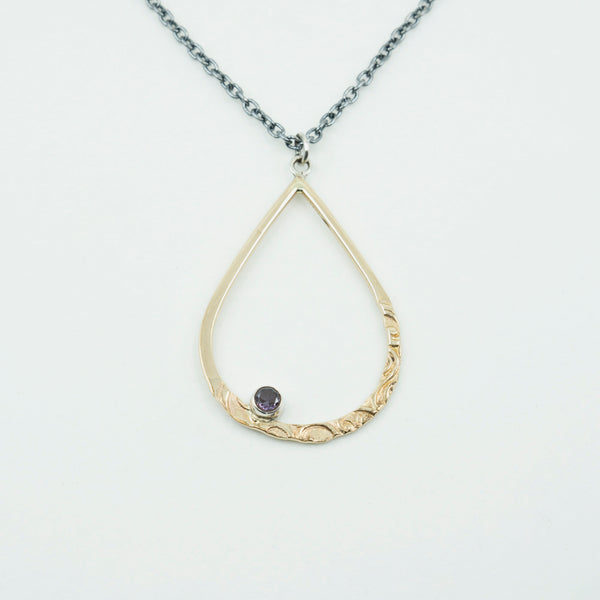 Close view of rain drop gold-filled pendant with a simulated alexandrite on a white background