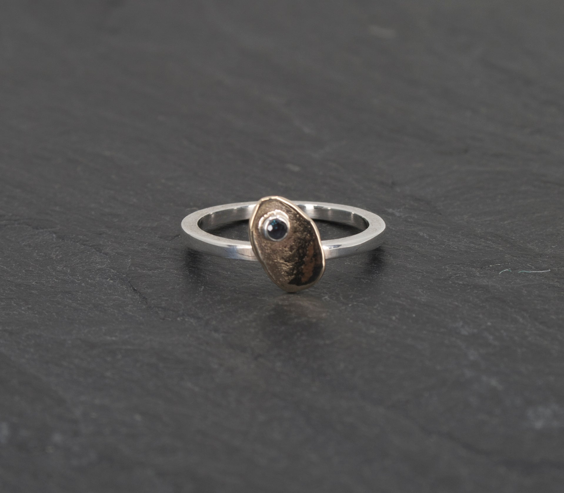 Small Irregular Gold Ellipse on a Sterling Ring with a Created Alexandrite on Slate Background