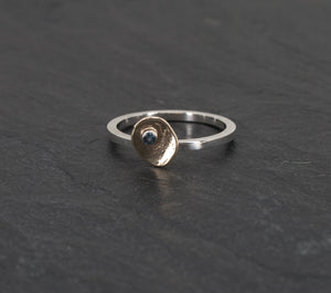 Small Irregular Gold Ellipse on a Sterling Band with a Montana Sapphire on a Slate Background