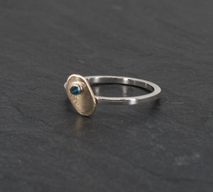 Small Irregular Gold Disk on a Sterling Ring with a London Blue Topaz on Slate Background