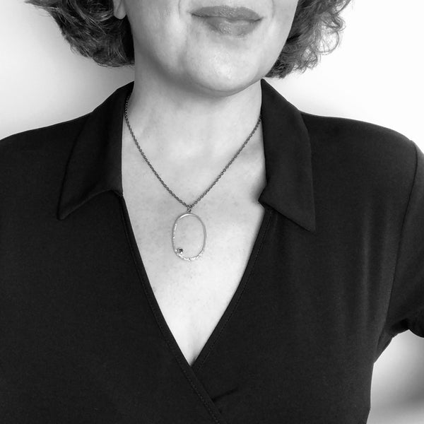 Black and white photo of artist modeling the Silver Oval Pendant with a Garnet for scale