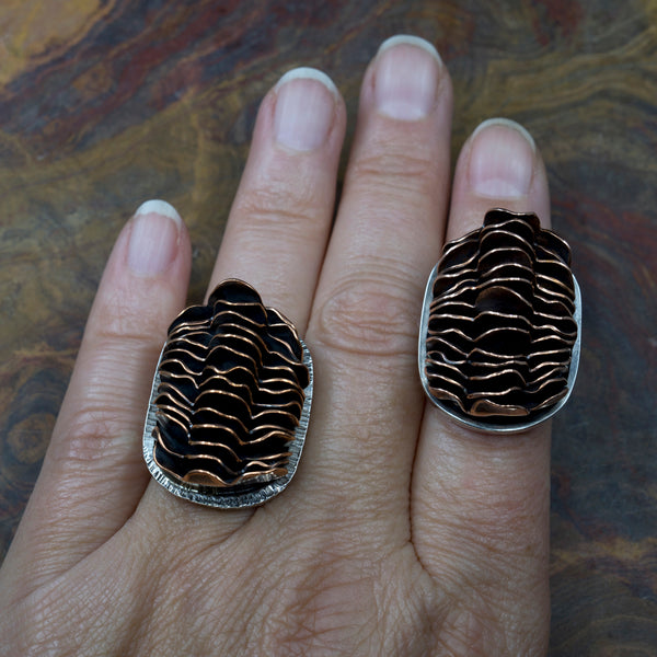 View of two different Sterling and Stacked Copper Rings on human hand for scale