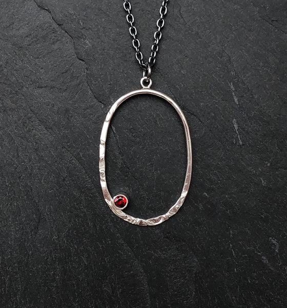 Close view of a Silver Oval Pendant with a Garnet on a slate background