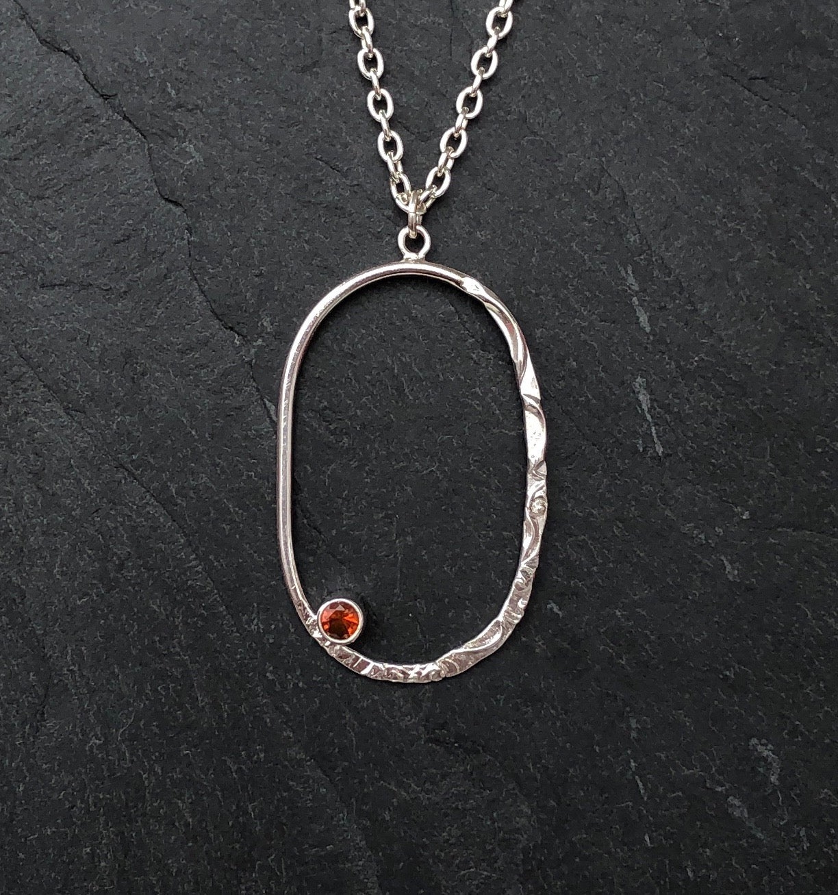 Close view of a Silver Oval Pendant with a Fire Opal  on a slate background
