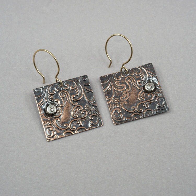 Embossed Copper Earrings with an Abstracted Flora and Scrolling Design