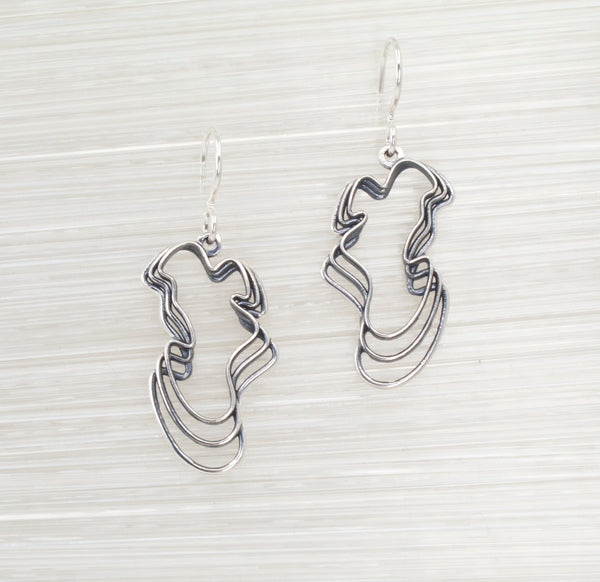 Sterling Water Waves Curvy Earrings on a Textured White Background