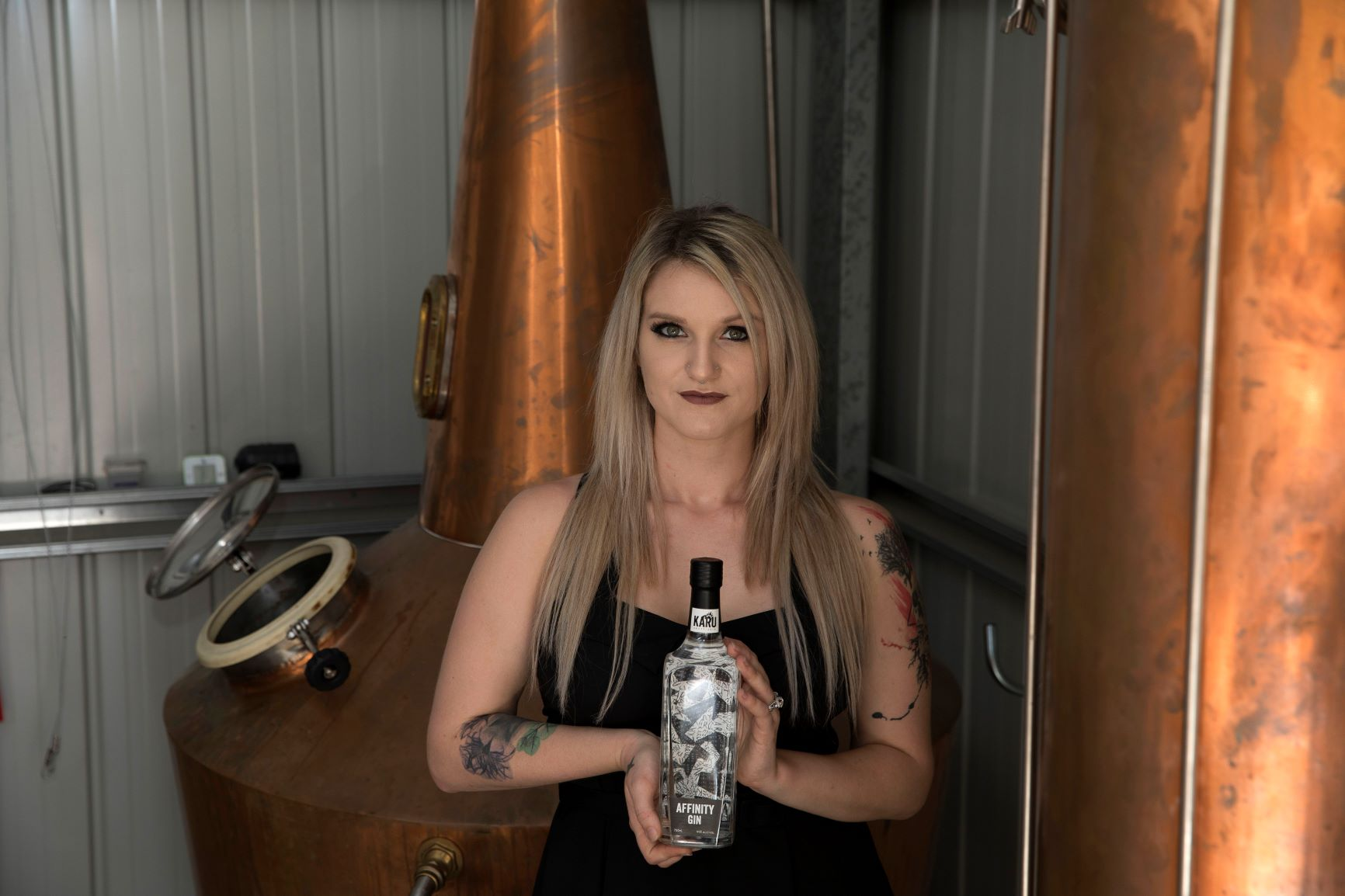 Ally Ayres from Karu Distillery holding Affinity Gin in front of their Copper Pot Still Calcifer