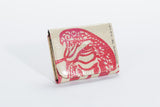 This is a bi-fold wallet made w/ recycled materials that has an over flap with snap, cotton interior lining with coin and card pockets, and plastic ID windows. It has a white background w/ a red cobra design on the front.
