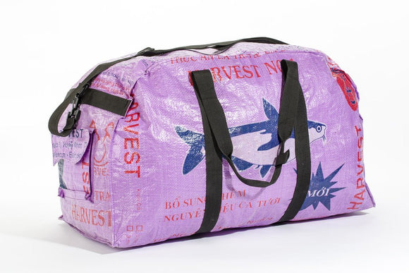 A large lilac duffle bag made from recycled material w/ blue fish design. Side cargo pockets, nylon strap, interior pockets.