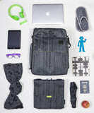 A suit grey Walter and Ray InTransit SLIM travel convertible backpack shown w/ carabiner, shoulder strap. head phones, slippers, Bendy Man light, scarf, eye glasses case, laptop, Insulated snack bag & passport.