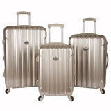 A 3-pc expandable metallic pale gold kensie Metallic Spinner Luggage Set w/ push-button gun metal trolley handle, top & side handles, fully-lined interior w/ zippered accessory pockets, detachable PVC bag, recessed TSA lock system.