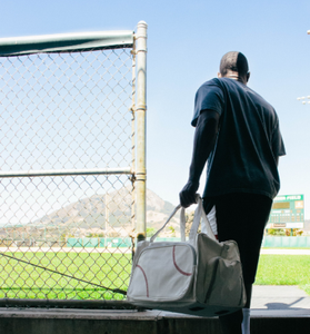 A baseball athlete carrying a Baseball Sport Duffel Bag made from actual baseball material w/ red baseball stitching onto a baseball field.