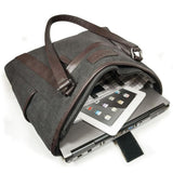 "An open charcoal 15.6"" Urban Laptop Tote w/ brown leather trim, handles, & padded computer compartment."