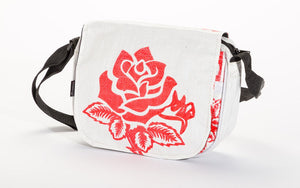 A small crossbody bag made w/ recycled material w/ a red rose pattern & w/ a black adjustable strap.