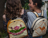 Two women wearing mini backpacks made w/ recycled material w/ a zip closure, exterior mesh cargo pocket, and interior zip pocket. One has a white background w/ an orange camel & the other has a lotus flower pattern on the front.