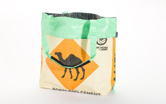 A barrel tote made with recycled material w/ a black camel on an orange diamond & a green top panel w/ green handles.