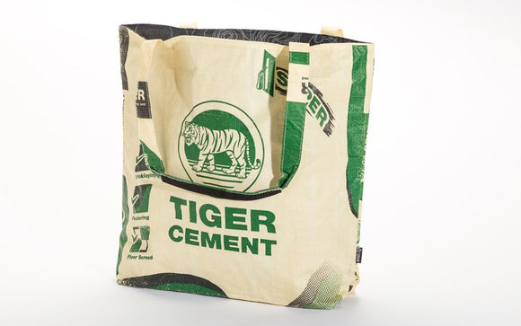 A large travel tote made w/ recycled material w/ a cream background & green tiger design on the front.