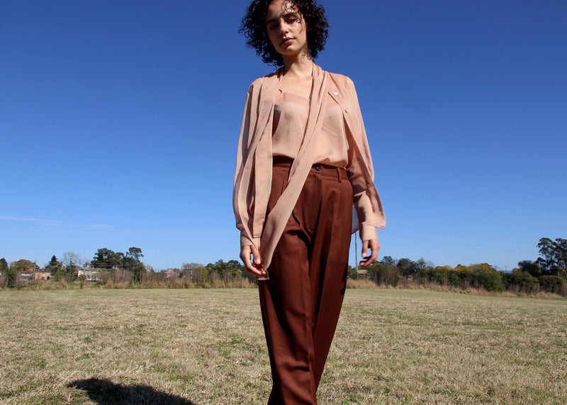 Maya wears the Amber Pussy-bow Blouse & Cami Set in Caramel Stripe with wool trousers from Laundromat