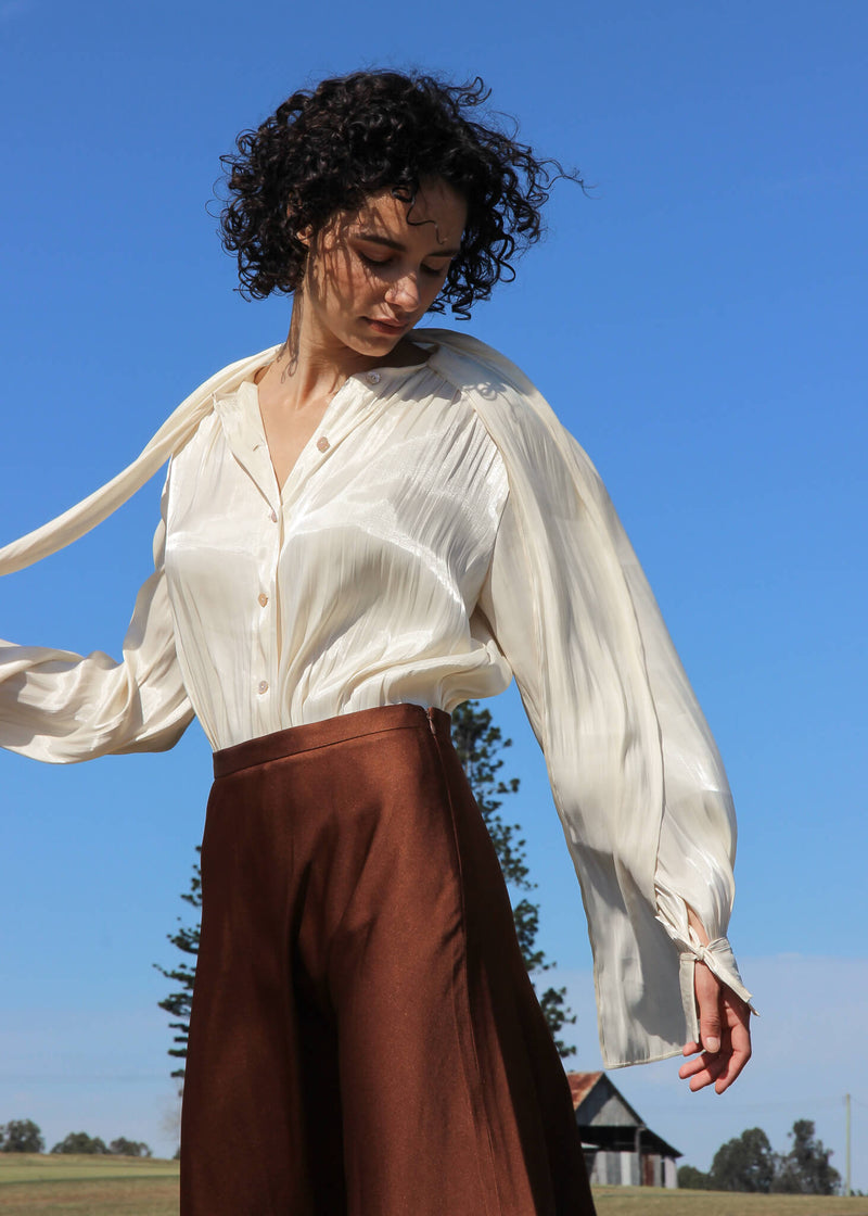 Maya wearing the Celeste Gathered Pussy-bow Blouse with brown skirt